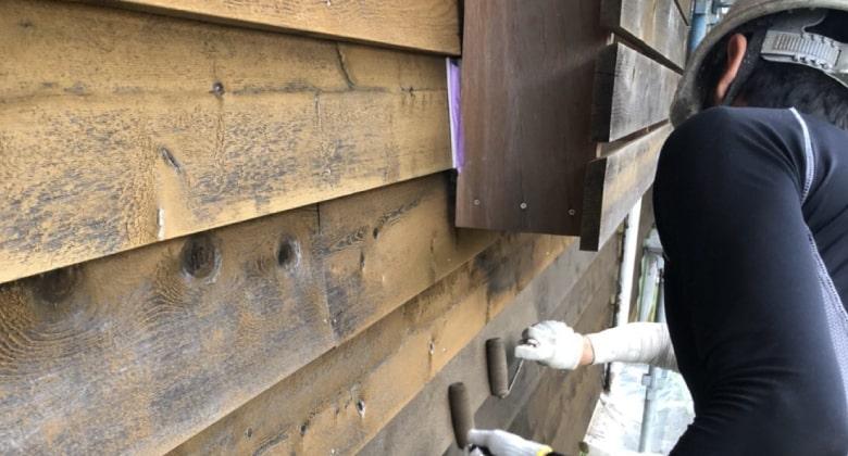 木材の壁を塗装している様子